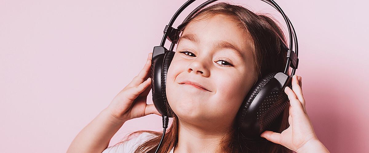 Treści dla dzieci. Cute little girl listening music wearing headphones.